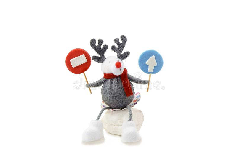 A toy deer holding a road sign. A toy deer seat and holding a road sign stock photography