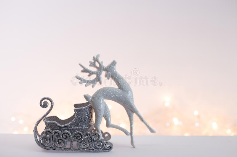 Toy deer. Toy silver sleigh with a white deer on the background of blurred Christmas lights. Picture in light colors stock photography