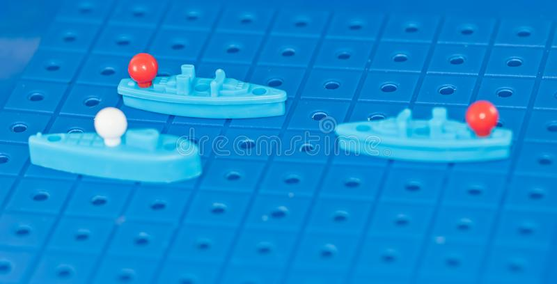Toy war ships and a submarine lined up to play a Board game. Toy destroyer surrounded by a corridor of underwater mines royalty free stock images
