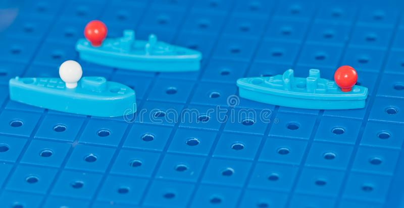 Toy war ships and a submarine lined up to play a Board game. Toy destroyer surrounded by a corridor of underwater mines stock images