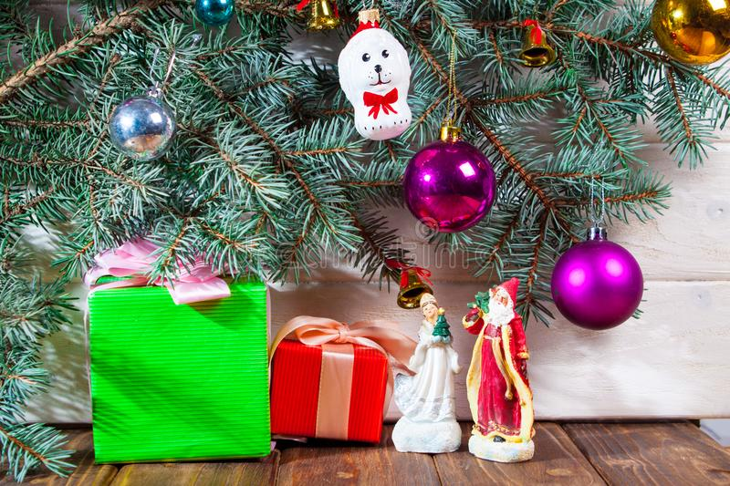 A toy dog in Santa hat and Christmas gifts on the background of coniferous branches. Christmas dog figurine background a toy dog in Santa hat and Christmas gifts royalty free stock photo