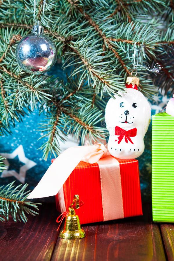 A toy dog in Santa hat and Christmas gifts on the background of coniferous branches. Christmas dog figurine background a toy dog in Santa hat and Christmas gifts stock photography