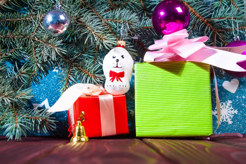 A toy dog in Santa hat and Christmas gifts on the background of coniferous branches. Christmas dog figurine background a toy dog in Santa hat and Christmas gifts stock photo