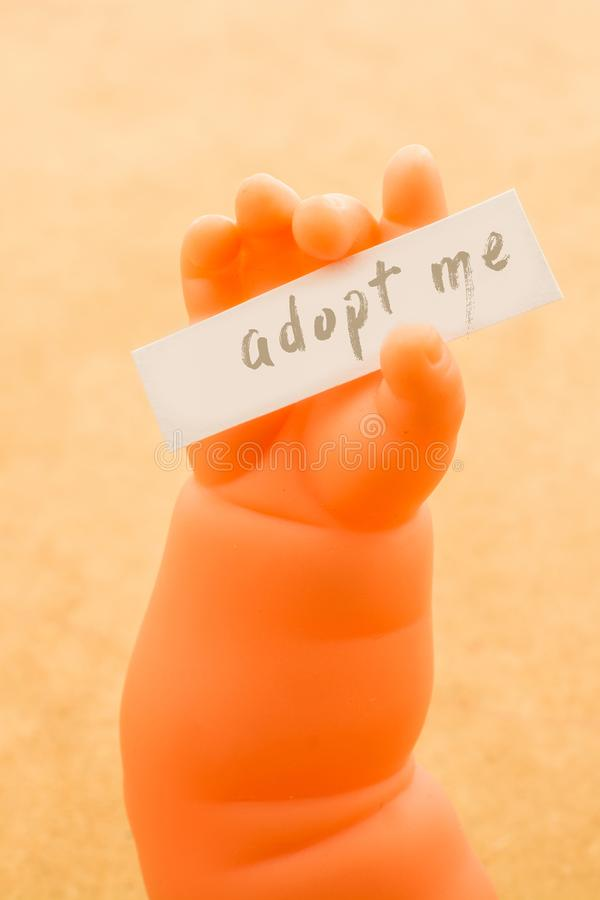 Toy doll hand holding paper with the word ADOPT ME royalty free illustration