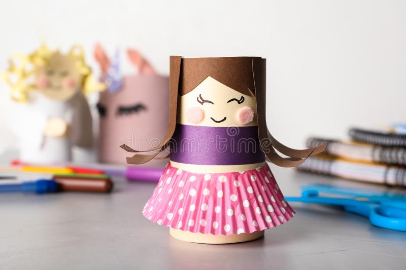 Toy doll made of toilet paper hub on table. Toy doll made of toilet paper hub on grey table stock photos