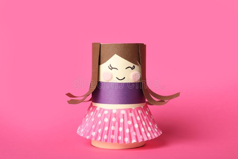Toy doll made of toilet paper hub on background. Toy doll made of toilet paper hub on pink background stock photography