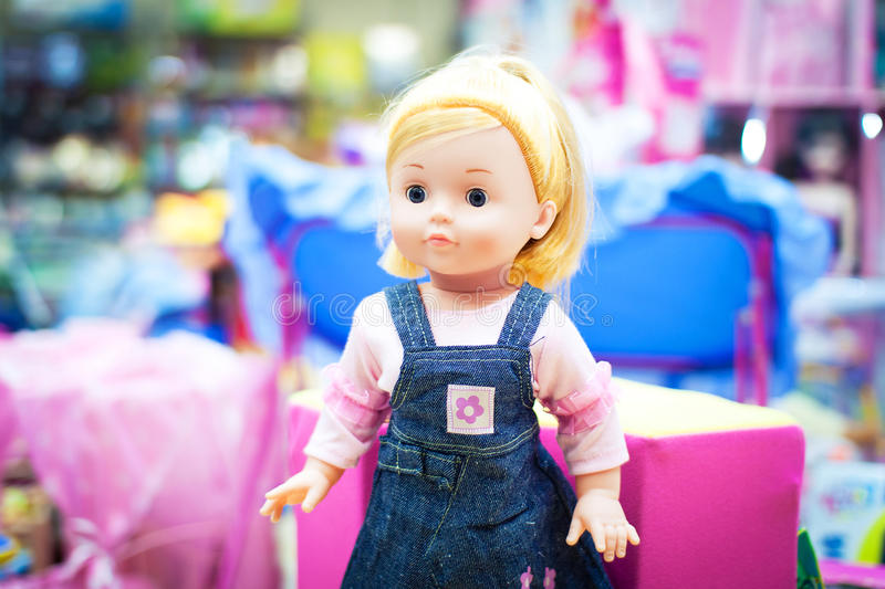 Toy doll in a store. Toy doll standing in a baby store surrounded by other toys stock images