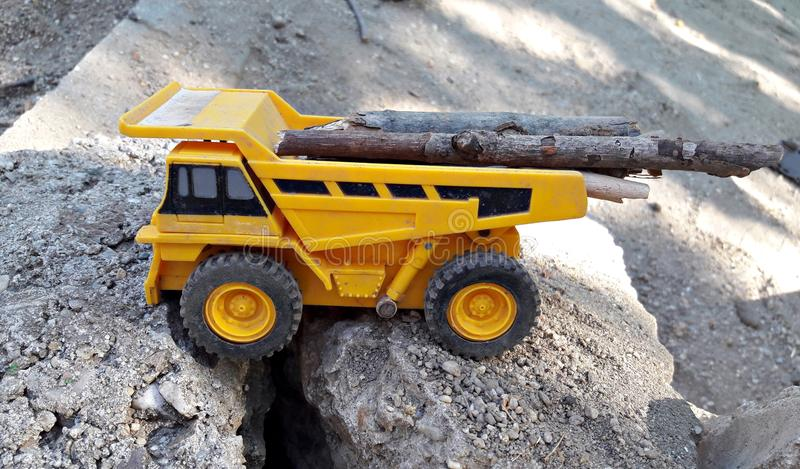 Toy dump truck carrying logs. On a rocky road royalty free stock photos