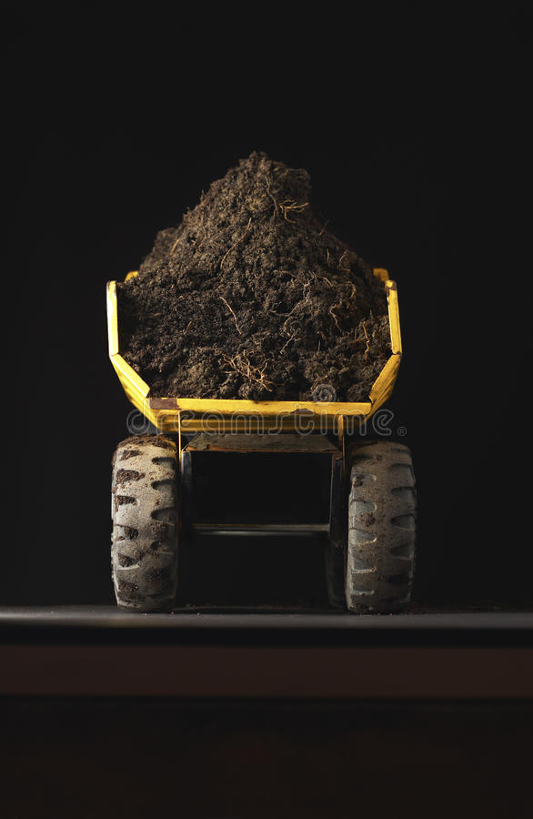 Toy dump truck with dirt back view stock photography