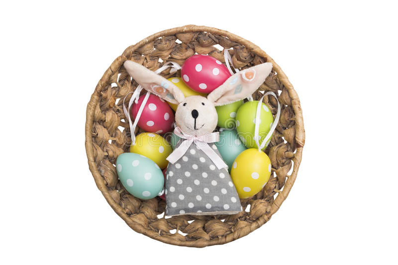 Toy Easter bunny in a wicker basket with dyed eggs stock photos