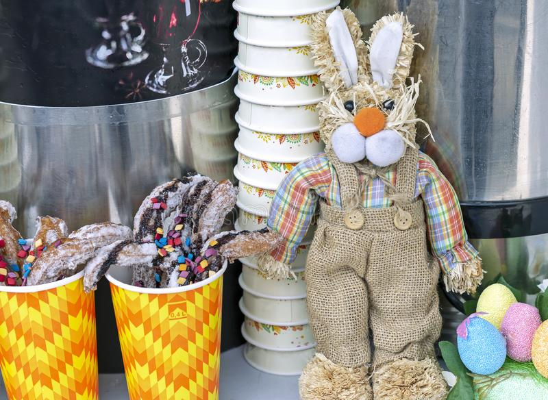 Toy Easter kanin och sötsaker på räknaren av ett gatakafé arkivbild