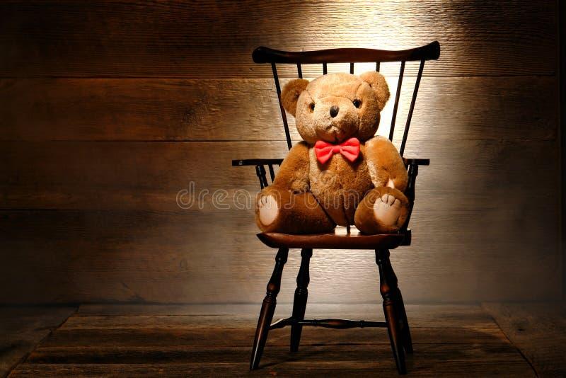 Toy för tappningnallebjörn på stol i gammalt husloft fotografering för bildbyråer
