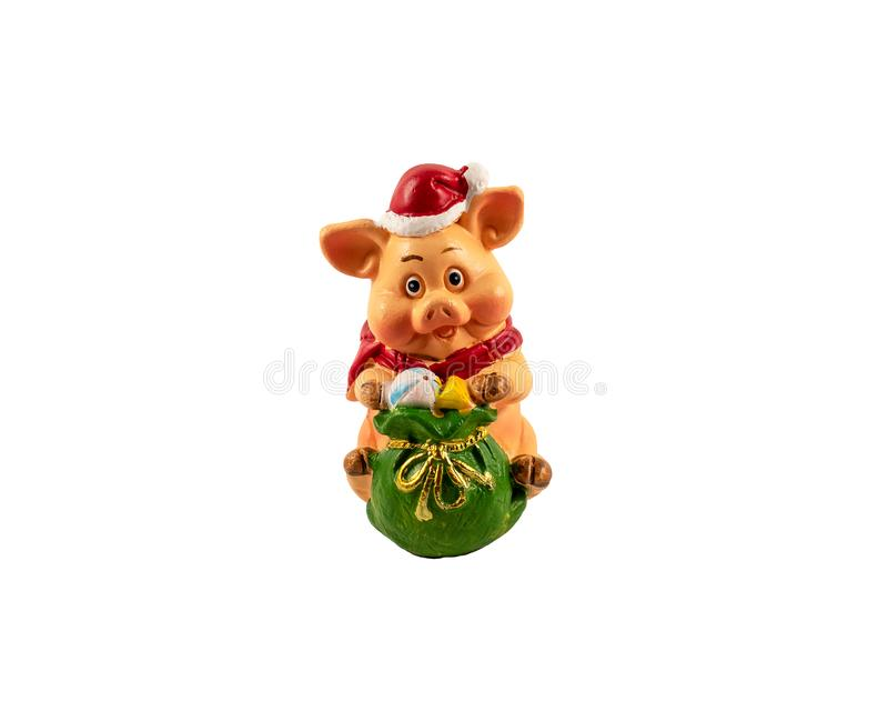 A toy figure of a pig in a new year`s red cap with a bag of gifts. Isolated on white background.  Selective focus.  royalty free stock photo