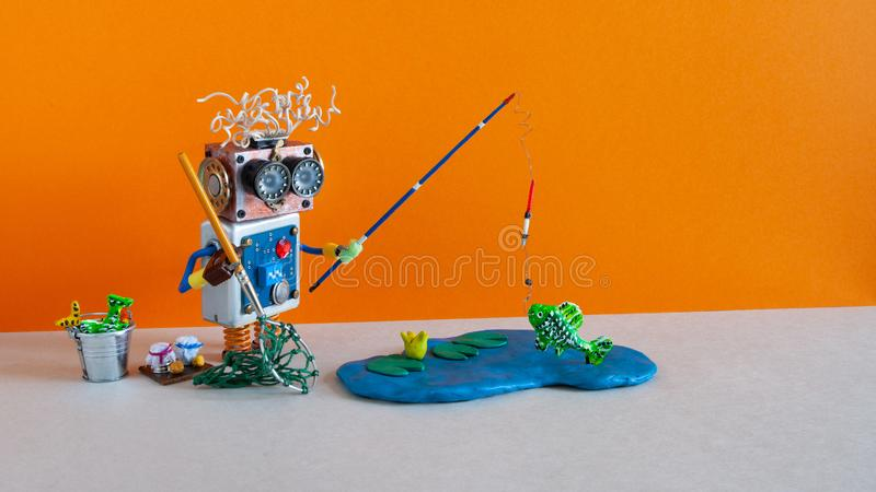 Toy fisherman caught big fish. Robotic fishing vacation concept. Funny angler with accessories rod bucket bait. Blue. Lake on orange background, copy space stock photo
