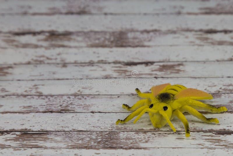 Toy Fly Insect plástico amarelo no fundo de madeira fotografia de stock