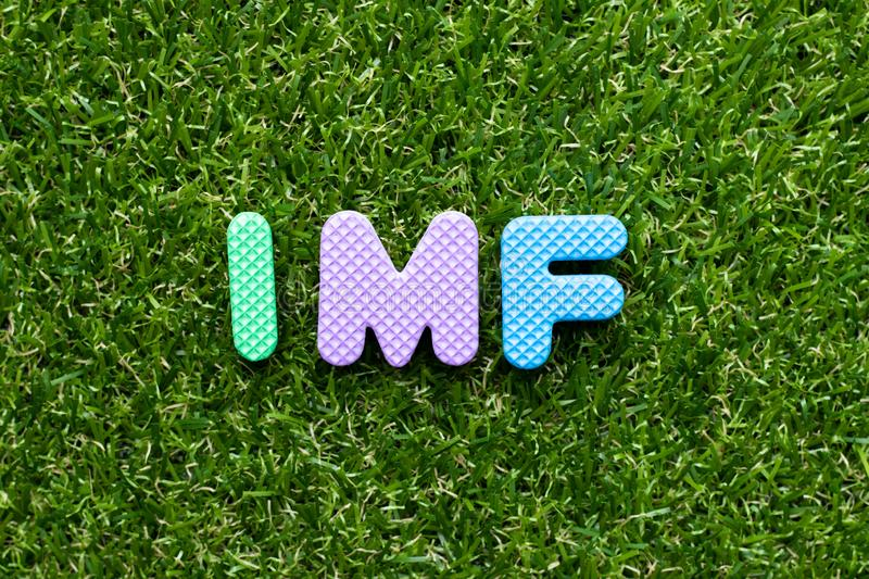 Toy letter in word IMF abbreviation of International Monetary Fund on green grass background stock photos
