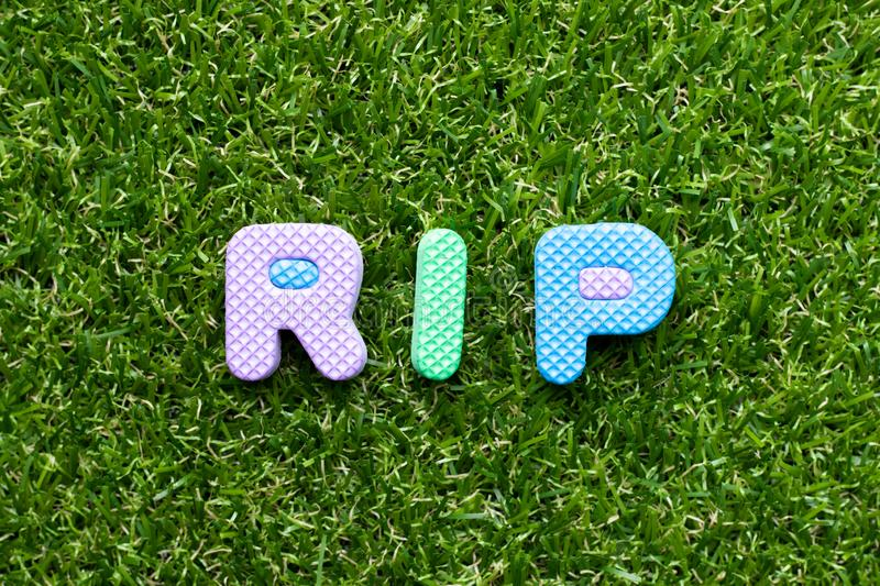 Toy letter in word RIP abbreviation of rest in peace on green grass background. Toy foam letter in word RIP abbreviation of rest in peace on green grass royalty free stock photo