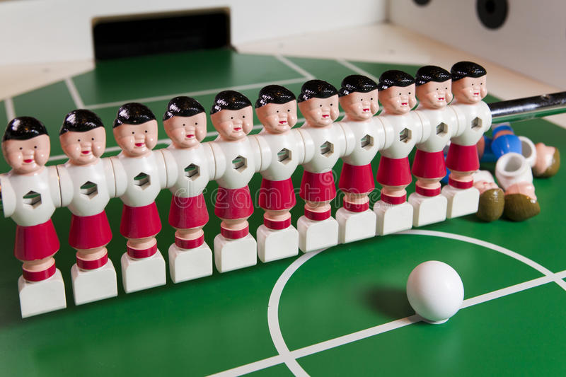 Toy football players stand on the football field, several figures have fallen, lie. Concept of excess, unnecessary people.  royalty free stock photos
