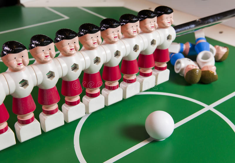 Toy football players stand on the football field, several figures have fallen, lie. Concept of excess, unnecessary people.  royalty free stock images
