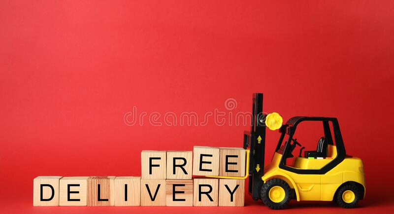 Toy forklift and cubes with words FREE DELIVERY on background, space for text. Logistics and wholesale concept. Toy forklift and cubes with words FREE DELIVERY stock photo