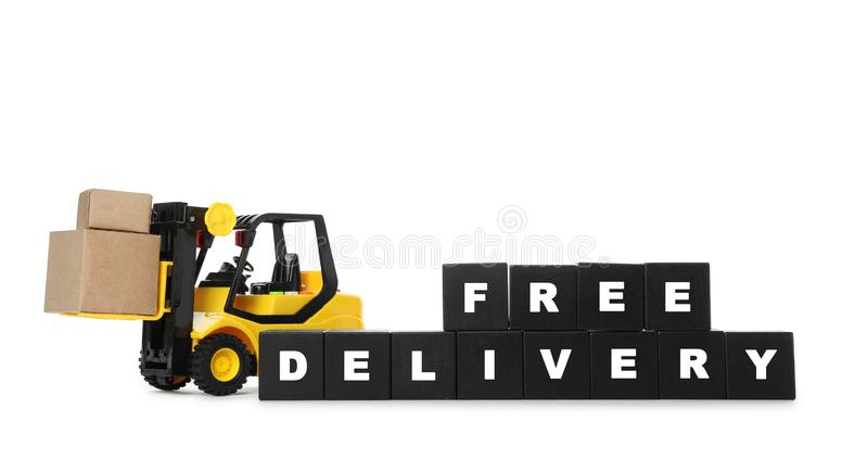Toy forklift and cubes with words FREE DELIVERY isolated. Logistics and wholesale concept. Toy forklift and cubes with words FREE DELIVERY isolated on white stock images