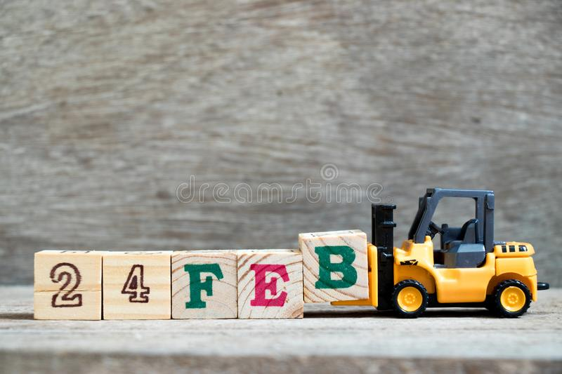 Toy forklift hold block B to word 24feb on wood background Concept for calendar date 24 in month February. Toy forklift hold block B to complete word 24feb on stock photo