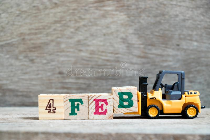 Toy forklift hold block B to word 4feb on wood background Concept for calendar date 4 in month February. Toy forklift hold block B to complete word 4feb on wood stock images