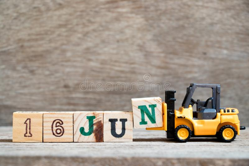 Toy forklift hold block N to complete word 16 jun on wood background (Concept for calendar date in month June. Day, organizer, event, note, time, week royalty free stock photos