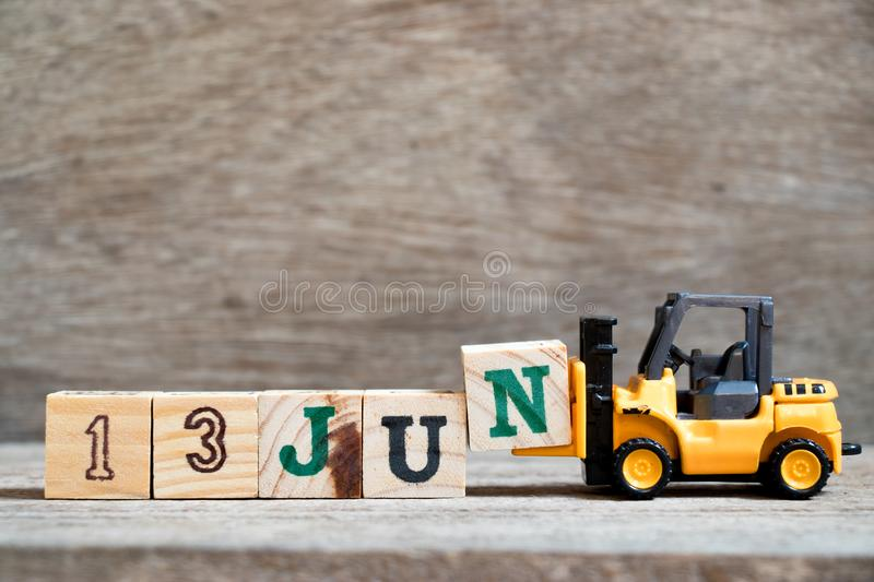 Toy forklift hold block N to word 13 jun on wood background Concept for calendar date in month June. Toy forklift hold block N to complete word 13 jun on wood stock photos
