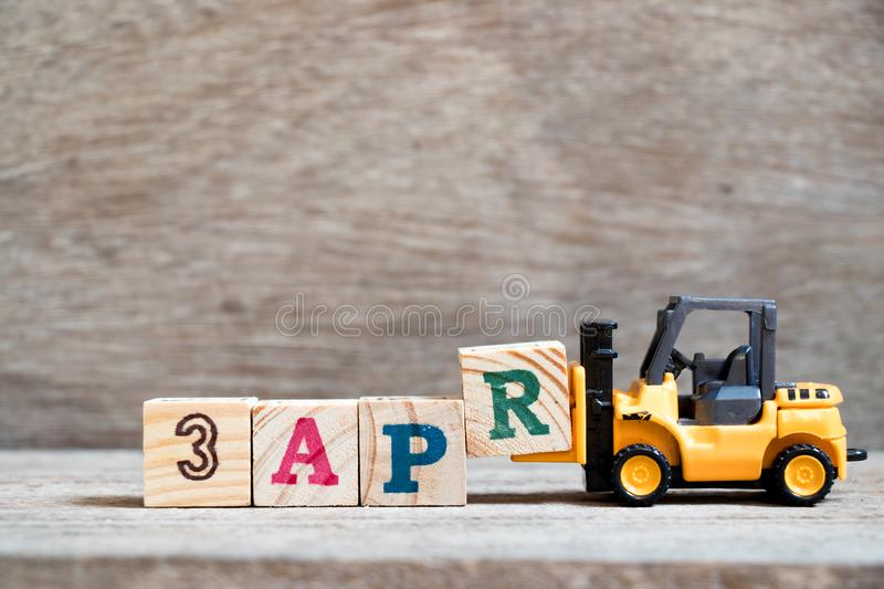 Toy forklift hold block R to word 3apr on wood background Concept for calendar date 3 in month april. Toy forklift hold block R to complete word 3apr on wood royalty free stock photography