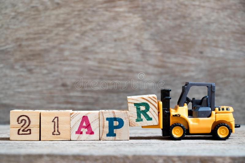 Toy forklift hold block R to word 21apr on wood background Concept for calendar date 21 in month april. Toy forklift hold block R to complete word 21apr on wood royalty free stock image