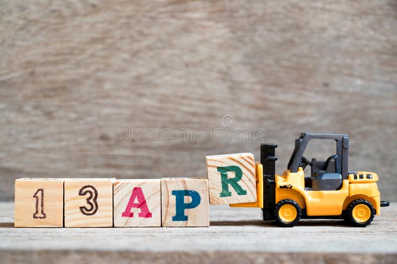 Toy forklift hold block R to word 13apr on wood background Concept for calendar date 13 in month april. Toy forklift hold block R to complete word 13apr on wood royalty free stock image