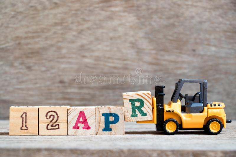 Toy forklift hold block R to word 12apr on wood background Concept for calendar date 12 in month april. Toy forklift hold block R to complete word 12apr on wood royalty free stock photos