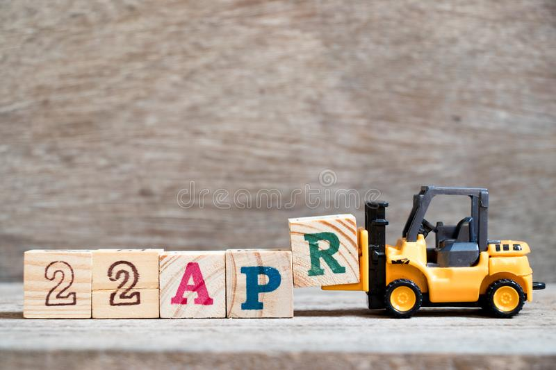 Toy forklift hold block R to word 22apr on wood background Concept for calendar date 22 in month april. Toy forklift hold block R to complete word 22apr on wood stock photo