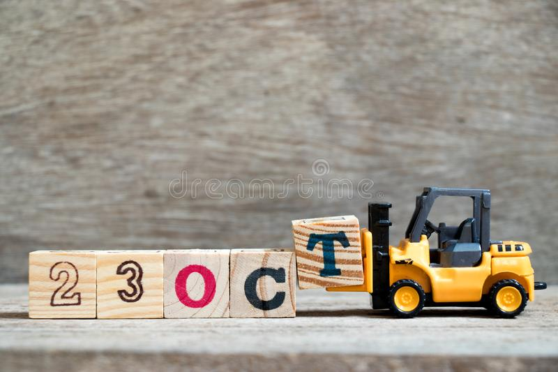 Toy forklift hold block T to word 23 oct on wood background Concept for calendar date in month October. Toy forklift hold block T to complete word 23 oct on wood stock photography