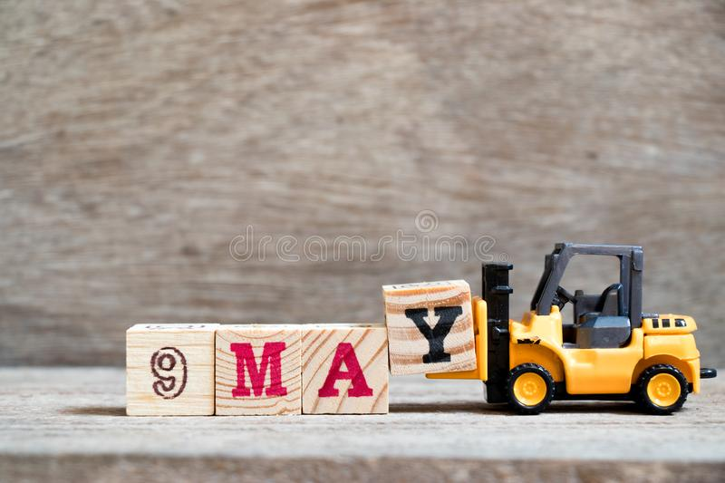 Toy forklift hold block Y to complete word 9 may on wood background & x28;Concept for calendar date for month May& x29;. Day organizer event note time week stock photos