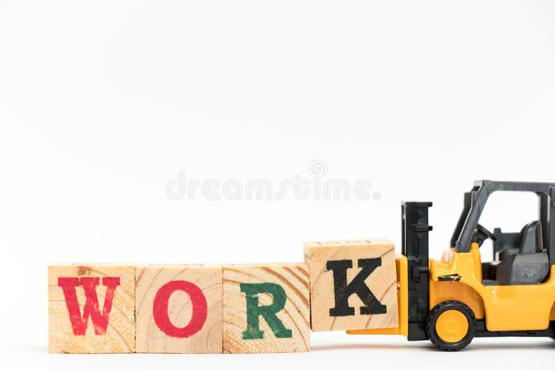 Toy forklift hold letter block K to complete word work on white background royalty free stock images