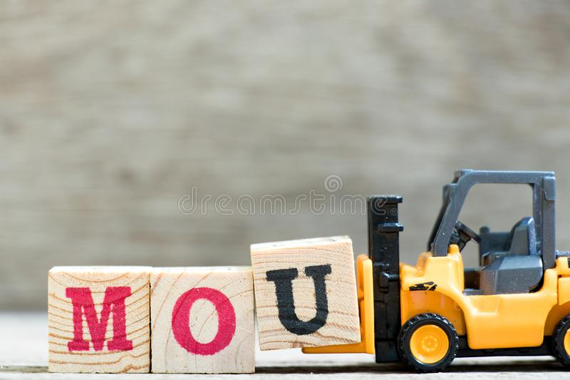 Toy forklift hold letter block u in word mou abbreviation of memorandum of understanding. On wood background stock photo
