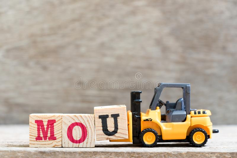 Toy forklift hold letter u in word mou abbreviation of memorandum of understanding on wood background. Toy forklift hold letter block u in word mou abbreviation royalty free stock images