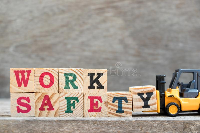 Toy forklift hold letter block Y to complete word work safety stock image