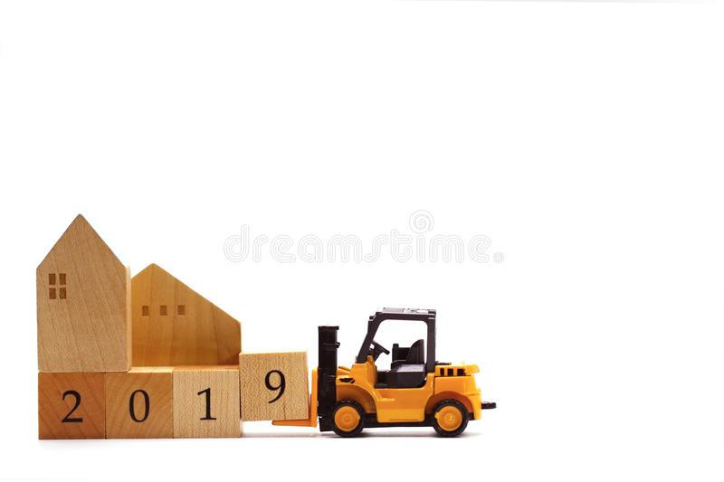 Toy forklift hold wooden letter block number 9 to complete year 2019 royalty free stock images
