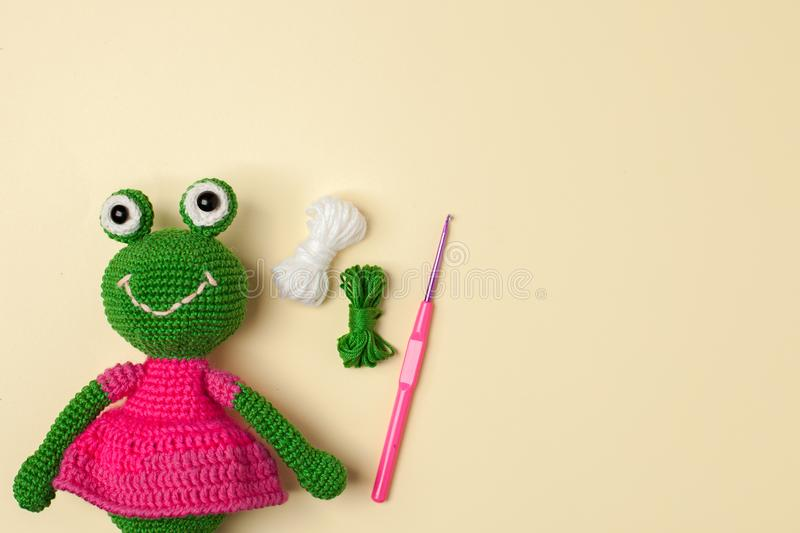 A toy frog in a dress, crocheted, on a gentle yellow background with tools and materials for creativity, an idea for needlework. stock images