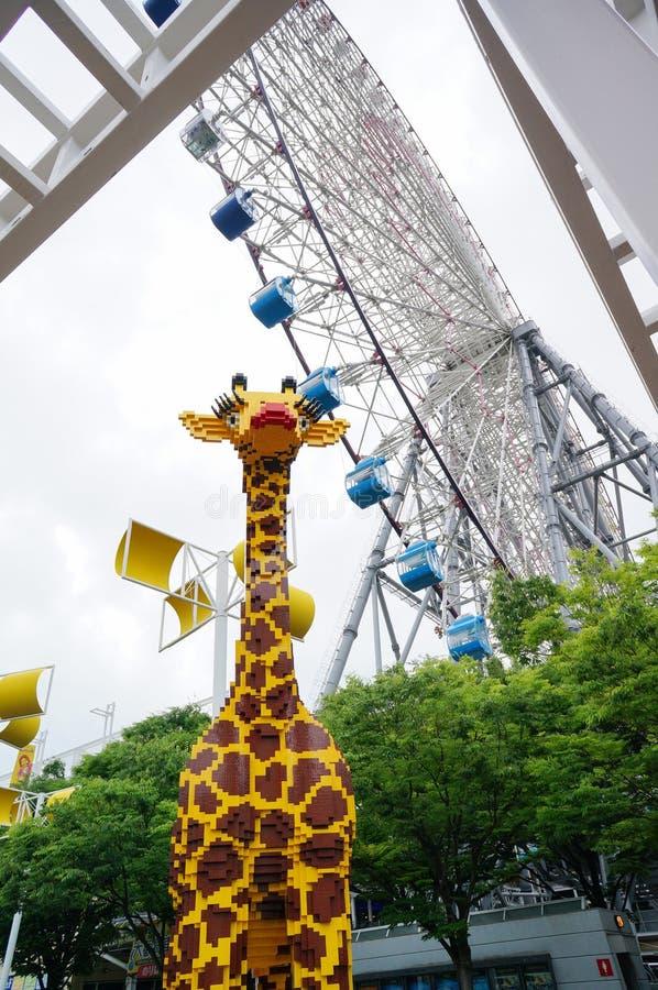 Toy Giraffe unter Ferris Wheel lizenzfreies stockfoto