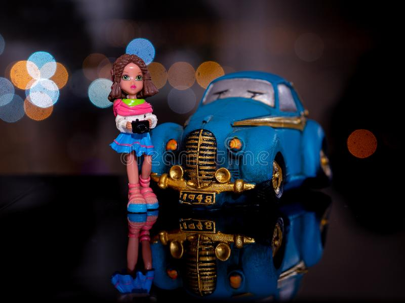 Toy girl standing at the blue car at night. On the background of beautiful bokeh royalty free stock photography