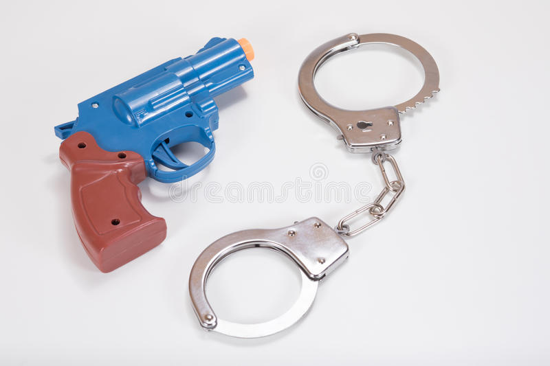 Toy handgun and handcuffs with white copy space stock images