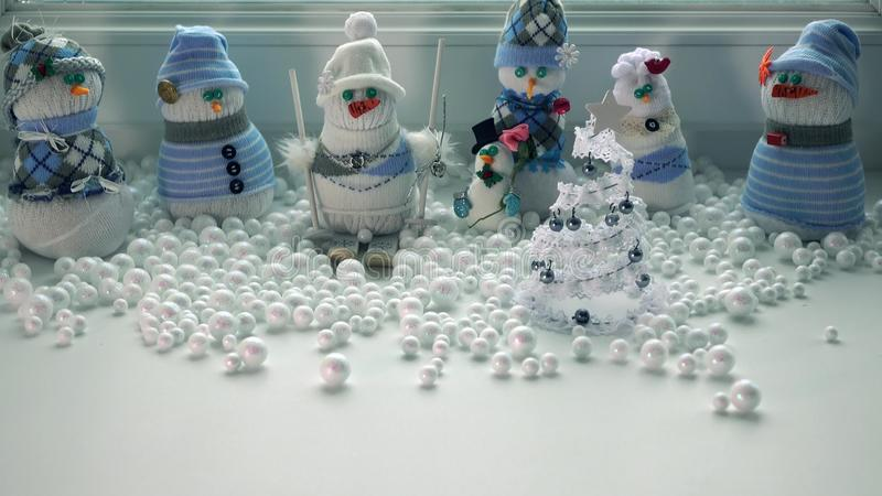 Toy handmade snowmen and snowstorm outside the window. Free space for inscription stock photos