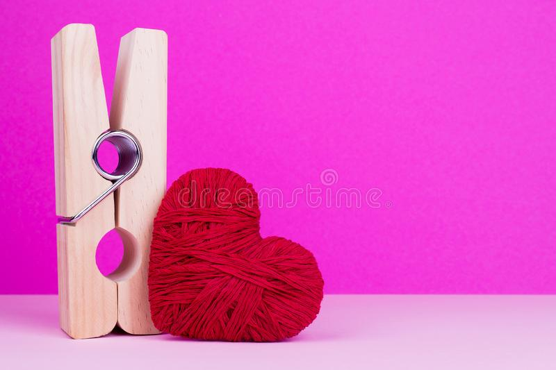 Toy heart and clothespin on pink background. Big wooden clothespin and red heart. St. Valentine`s Day royalty free stock photo