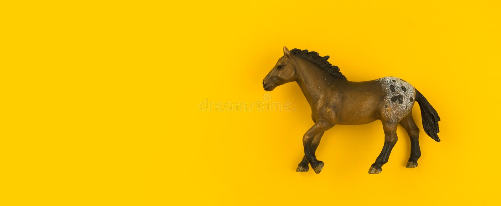 Toy horse made of plastic on a yellow background. Animal from the farm for the child. Pet artiodactyl stock images