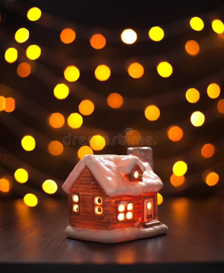 Toy house on a black background blurry multicolored lights. Christmas, winter, new year concept. Christmas composition. Toy house on a black background blurry stock images