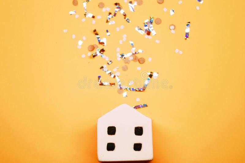 Toy house with confetti on yellow background. stock photo